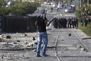 Palestinian throws stones towards Israeli police during clashes in Shuafat