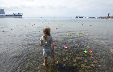 Girl looks at paper boats launched during celebrations for the 69th anniversary of the end of World War Two in the far eastern city of Vladivostok