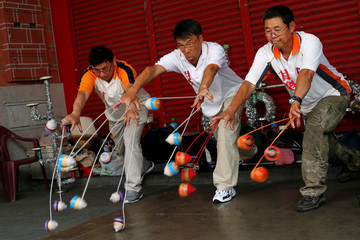 Members of the Sanxia Pinpoint Spinning Top Team throw 18 spinning tops simultaneously at Sanxia old street in New Taipei City, Taiwan