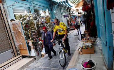 A man rides his bicycle through the Kasbah souk, in the old town of Tunis
