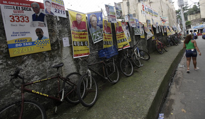 A woman walks past electoral posters at Santa Marta slum