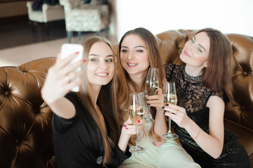 Three young girls are doing selfie photo in a restaurant