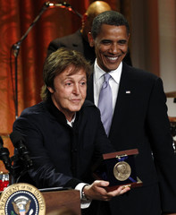 Paul McCartney holds his award next to U.S. President Barack Obama at the White House in Washington