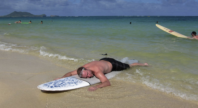 A tourist rests on his surfboard in Hawaii