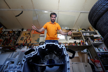 Jordanian graphic designer Abdelrahman Asfour, who turns car parts into furniture, works at his workshop in Amman