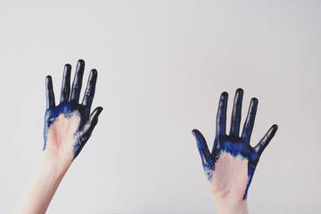 Painted blue hands are give up