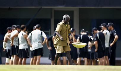 New Zealand's team players stand in a huddle as a ground worker walks past during a cricket practice session in Chennai