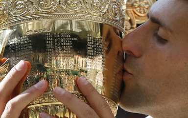 Novak Djokovic of Serbia kisses the winners trophy after defeating Roger Federer of Switzerland in their men's singles final tennis match at the Wimbledon Tennis Championships, in London