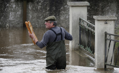 A resident brings French baguettes to his mother's flooded house after heavy rain falls in Chalette-sur-Loing Montargis