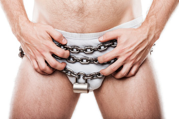 Naked man hands holding padlock locked chain over pants underwear