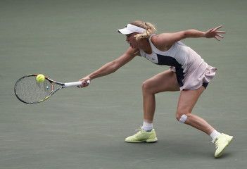 Wozniacki of Denmark returns a shot to Bencic of Switzerland during their Pan Pacific Open women's singles semi-finals tennis match in Tokyo