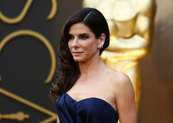 "Sandra Bullock, best actress nominee for her role in ""Gravity,""  wearing a navy Alexander McQueen gown  with Lorraine Schwartz jewels, arrives at the 86th Academy Awards in Hollywood"
