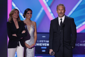 Actor Costner accepts the Lifetime Achievement Award as presenter Russo listens during the 20th Annual Critics' Choice Movie Awards in Los Angeles