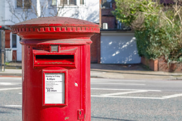 Iconic red English post box set against a de-focused street background