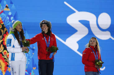 Joint gold medalists Switzerland's Gisin and Slovenia's Maze stand on the podium next to bronze mdealist Switzerland's Gut during the medal ceremony of the women's alpine skiing downhill race at the 2014 Winter Olympic Games in Sochi