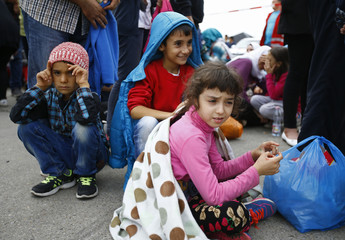 Migrant's children sit on the ground in Nickelsdorf