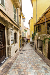 Narrow pedestrian street in Old Town of Cannes, France with sidewalk cafes, souvenir shops.