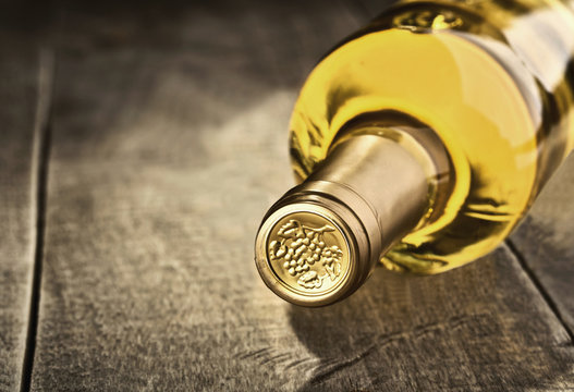 Bottle of dry white wine on a wooden background