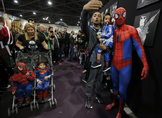 A participant dressed as superhero Spiderman poses for a picture with fans during the first edition of HeroFestival in Marseille