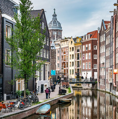 Amsterdam city view canal Singel with colorful dutch house, bridge, the Netherlands with Amstel river, Oudezijds Achterburgwal, reflection Basilica of St. Nicholas Church under dramatic sky in Summer