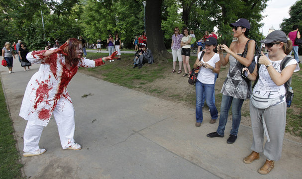 People take pictures of an enthusiast dressed as a zombie during a Zombie Walk procession in Prague