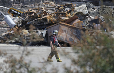 A firefighter walks past a pile of debris in Lac-Megantic