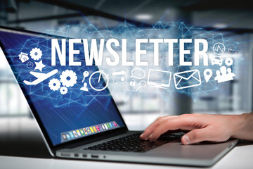 Concept of man holding futuristic interface with newsletter title and multimedia icons flying all around - Internet concept