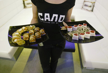 "A waitress carries dishes at a Ukrainian lard restaurant called ""Salo Lviv modern art museum"" in Lviv in western Ukraine"