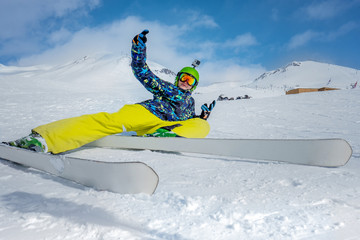 man with a mountain ski lies on the snow on a rough slope. Rejoices.
