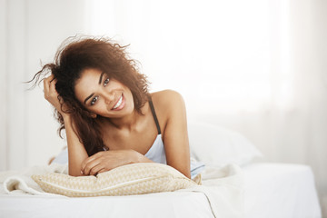 Beautiful happy tender african girl lying on pillow at home smiling looking at camera woke up on sunny day in the morning.