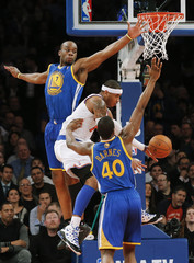 New York Knicks' Anthony loses the ball between Golden State Warriors' Landry and Barnes in their NBA basketball game in New York