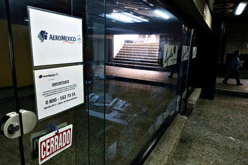 A woman walks past a closed office of Aeromexico in Caracas