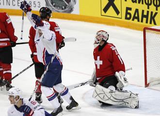 Switzerland's goalkeeper Stephan reacts as France's Auvitu celebrate scoring during their 2012 IIHF men's ice hockey World Championship game in Helsinki