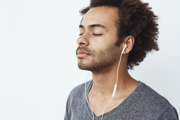 Close up of african man listening to music in headphones with closed eyes.