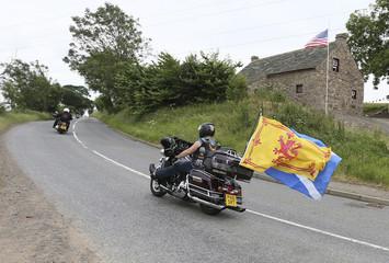 Harley Davidson enthusiasts pass the Davidson cottage near Aberlemno, Angus, Scotland
