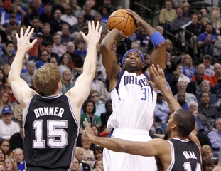Mavericks guard Terry shoots over Spurs forward Bonner  and guard Neal during their NBA basketball game in Dallas, Texas
