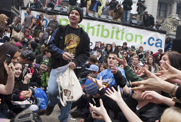 An organizer from the annual 420 marijuana rally throws free marijuana joints to the crowd at the Art Gallery in Vancouver.