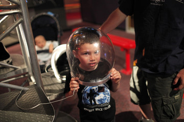 Michael Roth wears an astronaut helmet as he and his family visit the U.S. Astronaut Hall of Fame in Cape Canaveral