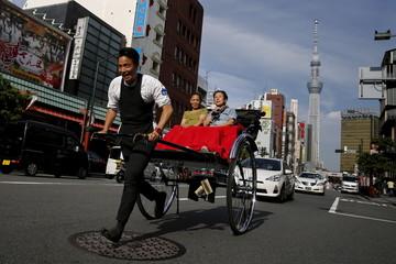 A man pulls people in rickshaw in Asakusa district of Tokyo
