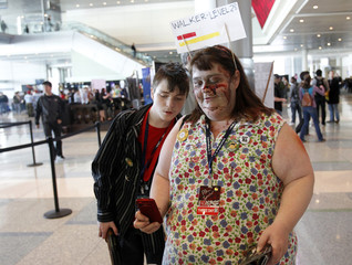 Dressed as zombies from the video game 'Dead Island' Dawn Angus and her son Andrew stop to take a picture of a vendor booth at the PAX East gaming conference in Boston