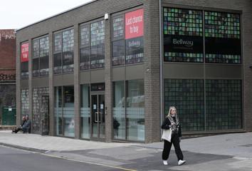A pedestrian walks past a Bellway housing development in London