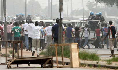 People stop an United Nations patrol with a roadblock in the neighbourhood of Abobo in Abidjan