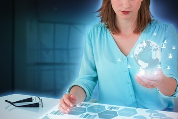 Composite image of businesswoman sitting at desk and using digit