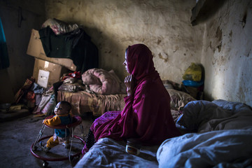 A woman sits at her house in Saidpur village in Islamabad