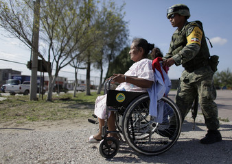 A soldier helps a woman bound to a wheelchair as part of a social assistance program in San Fernando, in the Mexican state of Tamaulipas