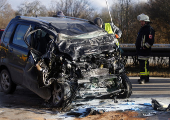Firefighters stand around the car wreckage of a wrong-way driver on the highway A92 near Moosburg