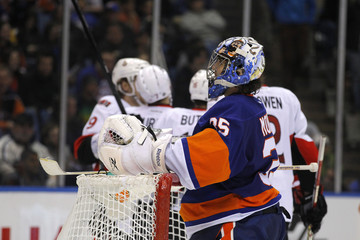 New York Islanders goalie Al Montoya reacts after giving up a goal to the Ottawa Senators who celebrate in the background in second period action during their NHL hockey game in Uniondale