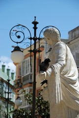 Marble statue with a pigeon on its hand in the Plaza de las Flores, Cadiz, Spain.