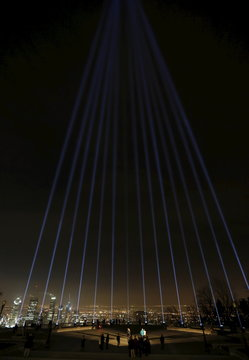 Fourteen blue beams of light are projected during a vigil to remember the victims of a mass shooting in Montreal