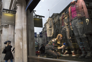 A shop worker adjusts a window display in a  Ted Baker store in London, Britain